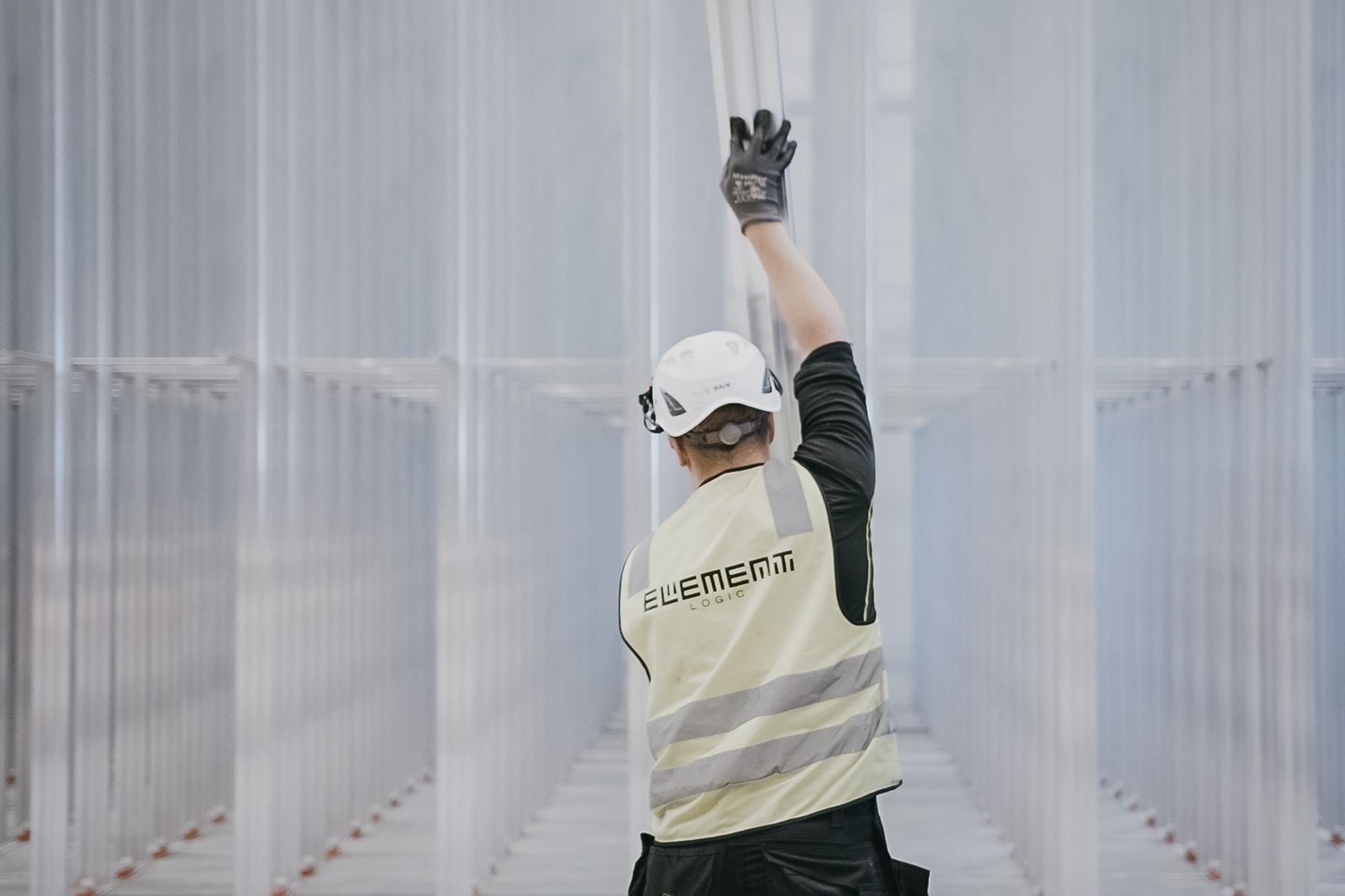 A man in a helmet and a yellow west is building the AutoStore grid consisting of aluminium columns.